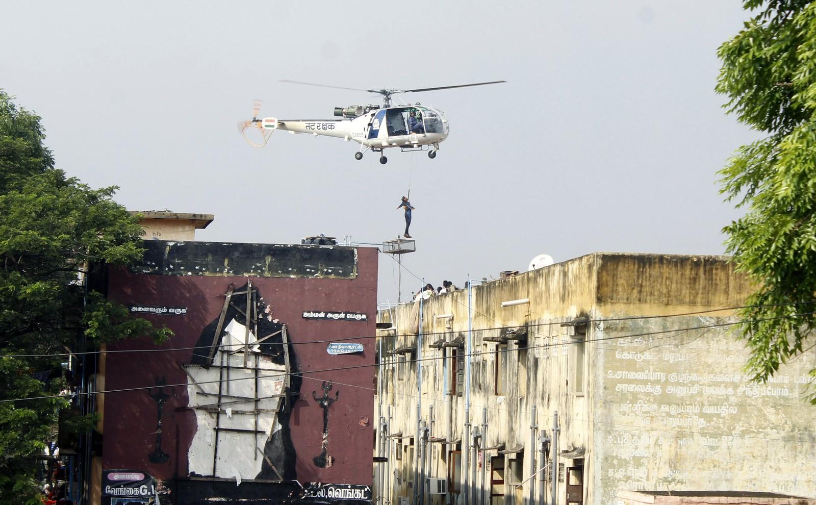 En mann blir løftet opp av et helikopter fra en bygning som er omringet av vann. Dette er det kraftigste regnfallet på hundre år i delstaten Tamil Nadu i India.