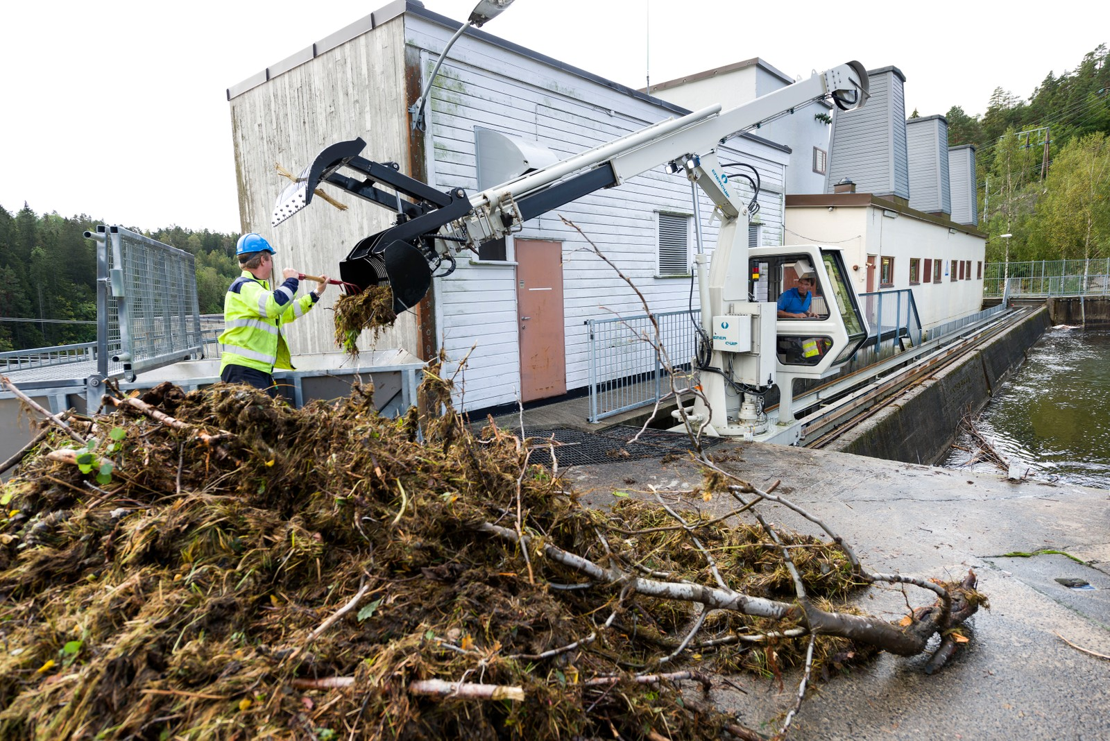 Store vannmengder ved Evenstad kraftverk. Trygve Thaule tar ut drivved frå grindrensen som Geir Klevene styrer.