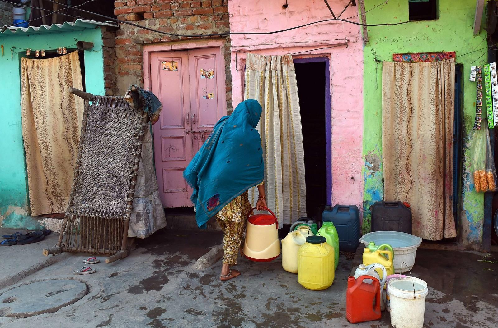 En indisk kvinne henter vann fra en offentlig vanntank i New Delhi.