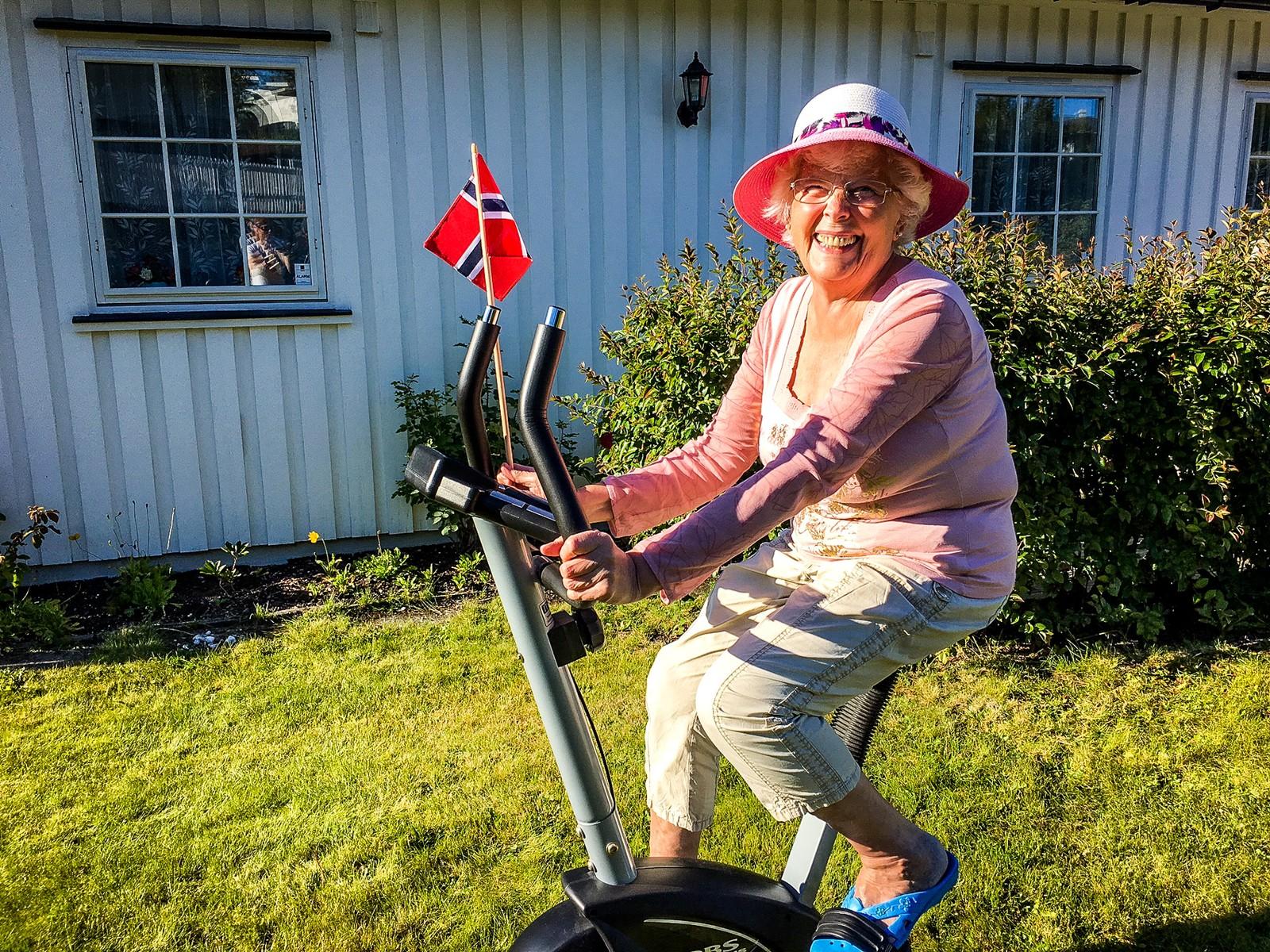 Aud Klæbo følger sykkelrittet syklende på ergometersykkelen i hagen, mens rytterne suser forbi.