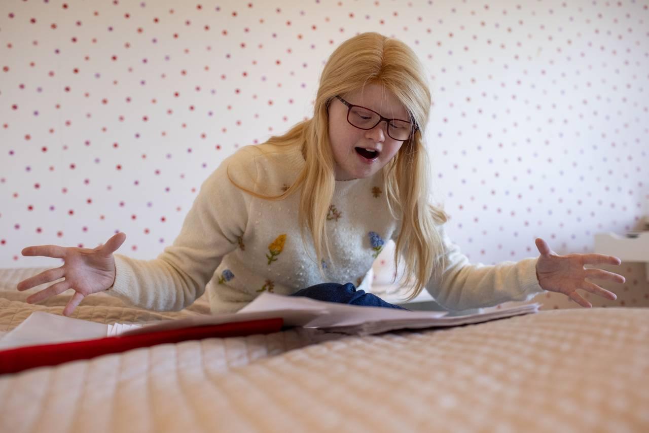 Bentine sitter i sengen sin på rommet. Hun øver på sanger og replikker.