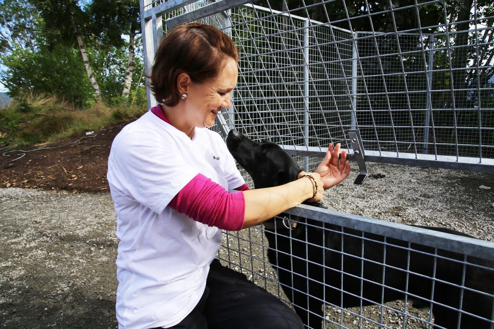 Nina Andrea Blakstad sammen med en av hundene på gården.