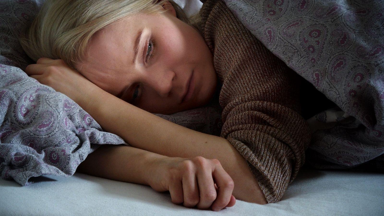 Sara ligger på siden i senga. Dyna er trukket nesten opp til ansiktet. Armene ligger som beskyttelse foran ansiktet. Hun ser ned.