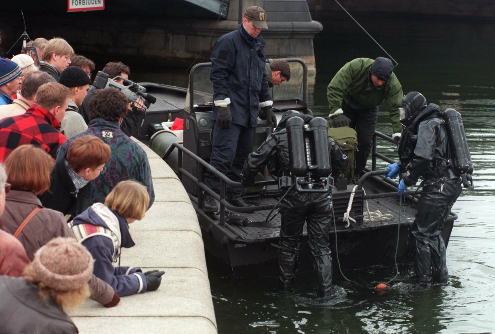 Politiets dykkere på veg opp fra vannet ved Tegelbacken i Stockholm, etter å ha dykket etter våpenet som skal ha blitt brukt til å drepe Olof Palme. Det ble funnet en pistol på bunnen under søket.