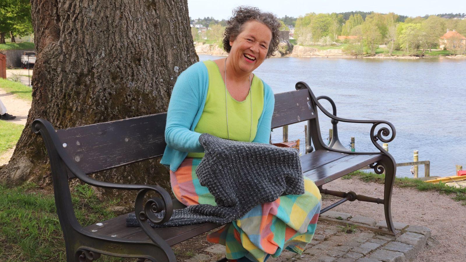 En dame sitter på en benk med genseren i hendene