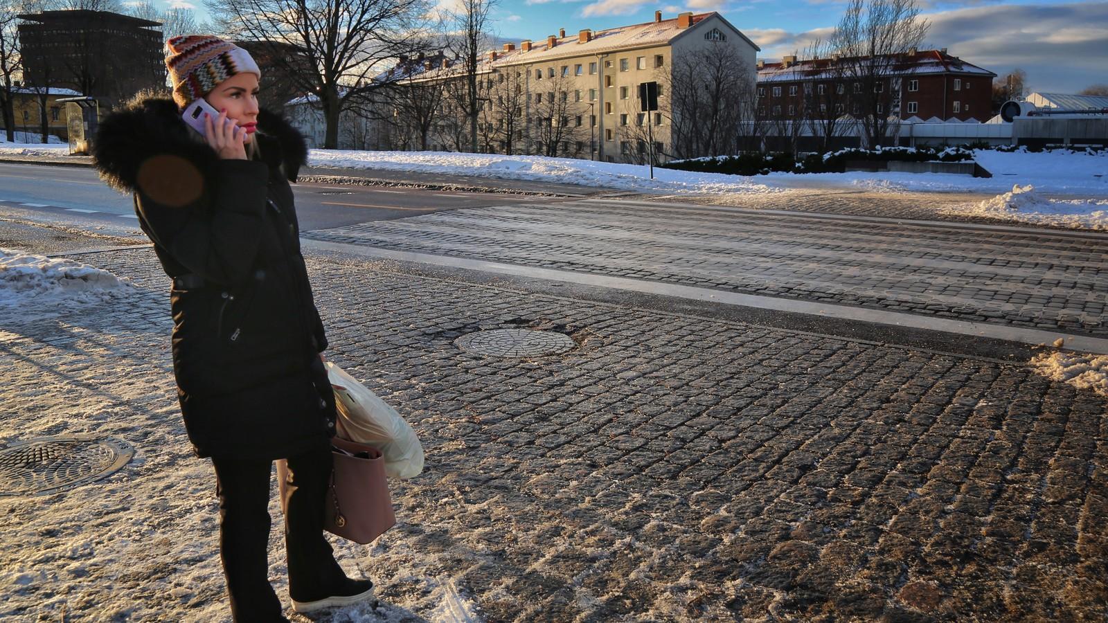 Ung kvinne ved en gate med blokker i bakgrunnen. Hun snakker i mobiltelefon og har vinterklær på seg. Ingen biler i gata.