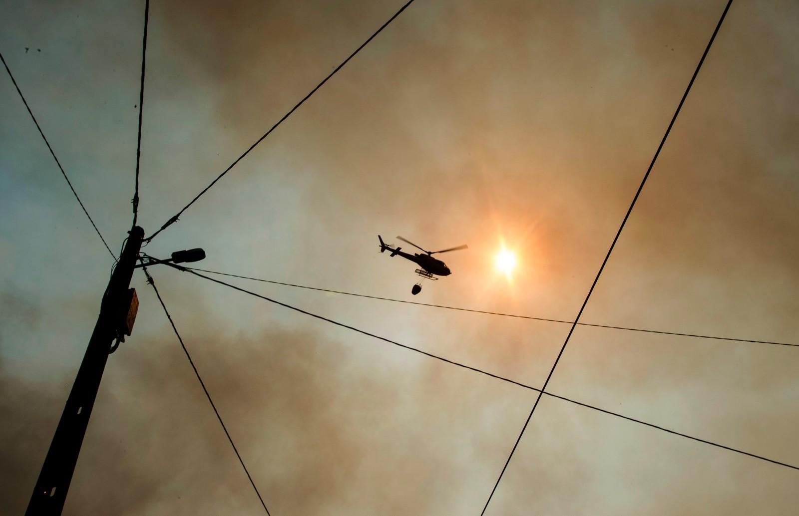 Helikopter flyr inn vann til brannområdene.