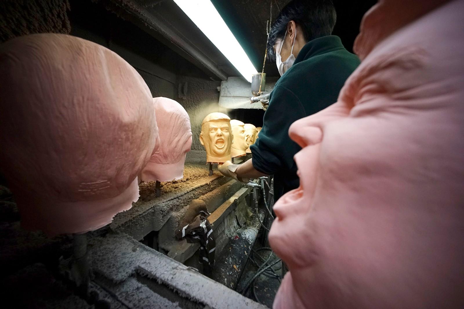 En arbeider sprayer farge på masker som skal forestille Donald Trump i Saitama i Japan. Etter valget har de 23 som har jobbet der jobbet hele døgnet for å kunne levere nok masker. De må nå produsere 350 masker hver dag, mot 45 før valget.