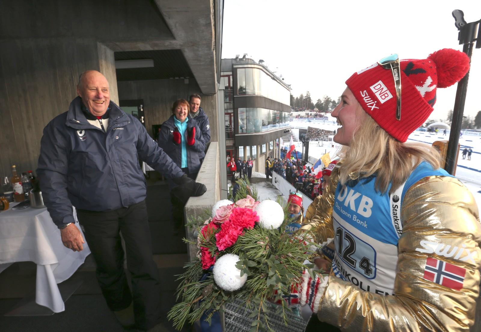 Stafett kvinner VM i skiskyting i Holmenkollen fredag. Kong Harald hilser på Marte Olsbu.