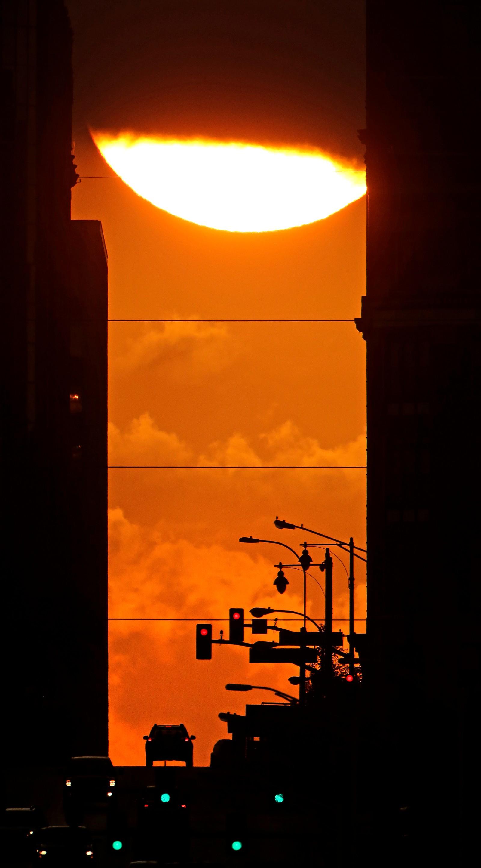 Solen titter fram mellom to bygninger i Kansas, USA. Onsdag ble begynnelsen på høsten markert.