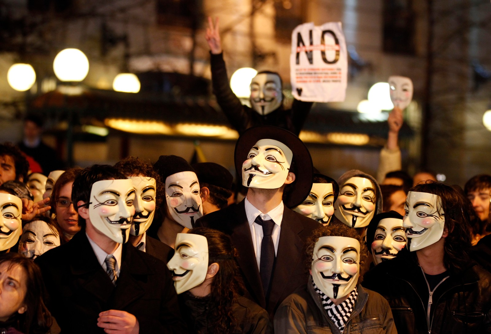 Demonstrators wearing Guy Fawkes masks protest against Spain's Culture Minister Angeles Gonzalez-Sinde and a new legislation yet to be passed, which would give the government the power to close down web pages containing links to copyrighted content such as films and music, in front of the Spanish Culture Ministry in Madrid February 13, 2011. REUTERS/Sergio Perez (SPAIN - Tags: SOCIETY IMAGES OF THE DAY CIVIL UNREST POLITICS)