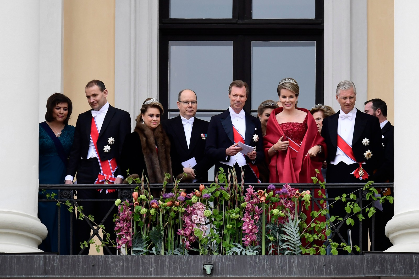 Kongeparet med kongelige gjester hilser publikum fra slottsbalkongen i anledning sin 80-årsfeiring. Fra v.: Eliza Reid, Islands president Gudni Johannesson, storhertuginne , , Maria-Teresa av Luxembourg, fyrst Albert av Monaco, Storhertug Henri av Luxembourg, Dronning Mathilde og Kong Philippe av Belgia,