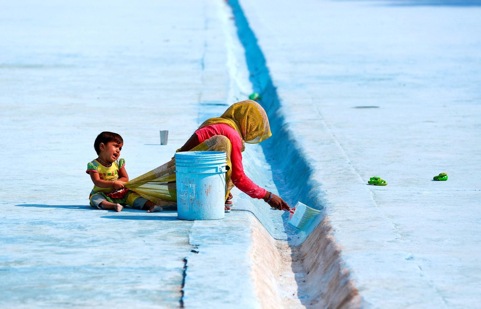 En kvinne maler bunnen til en dam i Delhi i India.