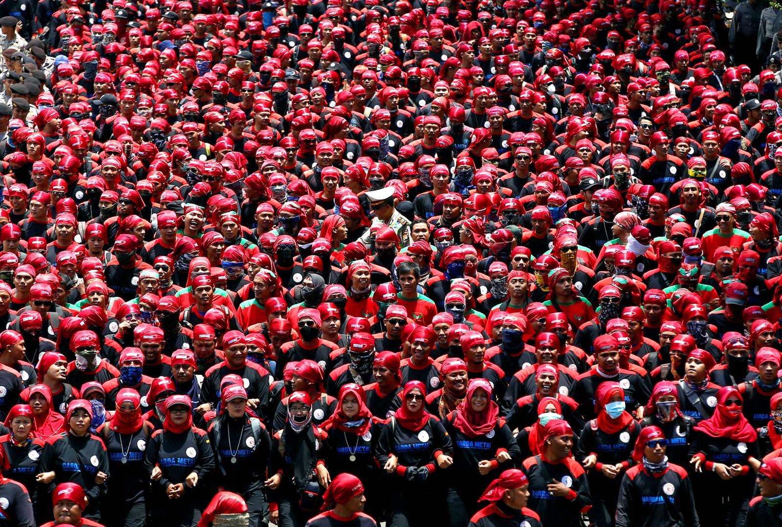 Tøff dag på jobben. Finner du politimannen? Bildet er fra en fagforeningsdemonstrasjon mot skatteamnesti i Jakarta i Indonesia den 29. september.