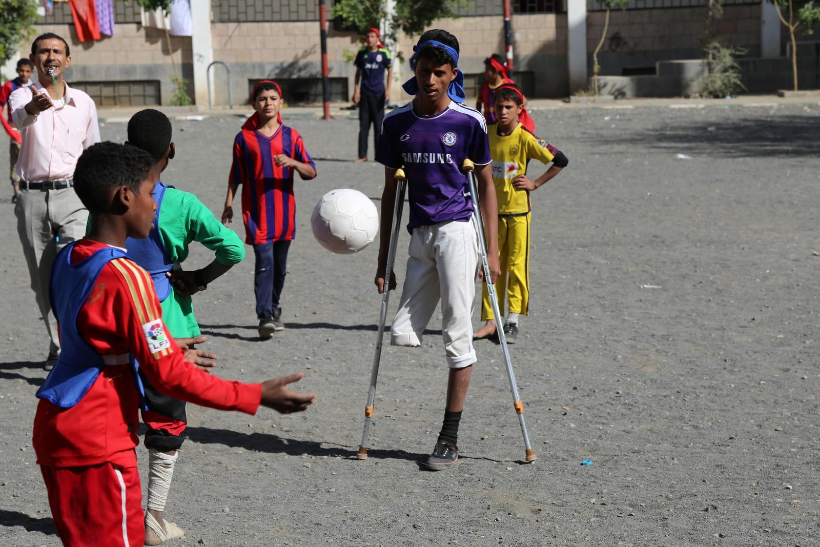 Rafik (i lilla) spiller fotball med et ben på Al Zubairi-skolen i Sana i Syria, i oktober i 2015. Han mistet det andre benet mens han spilte fotball. En bombe landet like i nærheten og drepte vennen hans på åtte år.