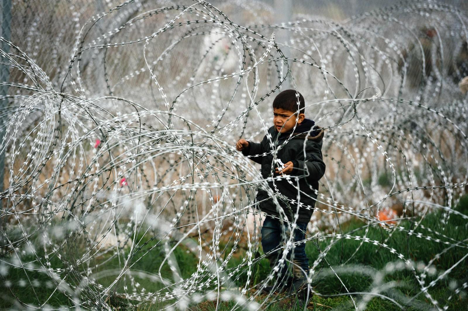 En gutt står mellom piggtrådgjerder nær den gresk-makedonske grensa. Tusener av mennesker oppholdt seg nær den greske byen Idomeni i håp om å få krysse grensa til Makedonia.