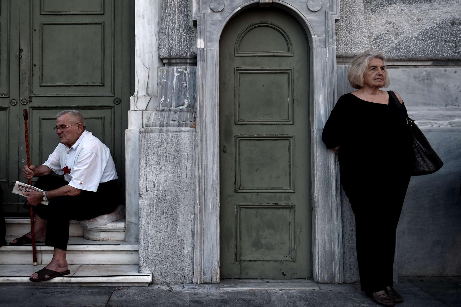 To eldre grekere venter på at en bank i Aten skal åpne.