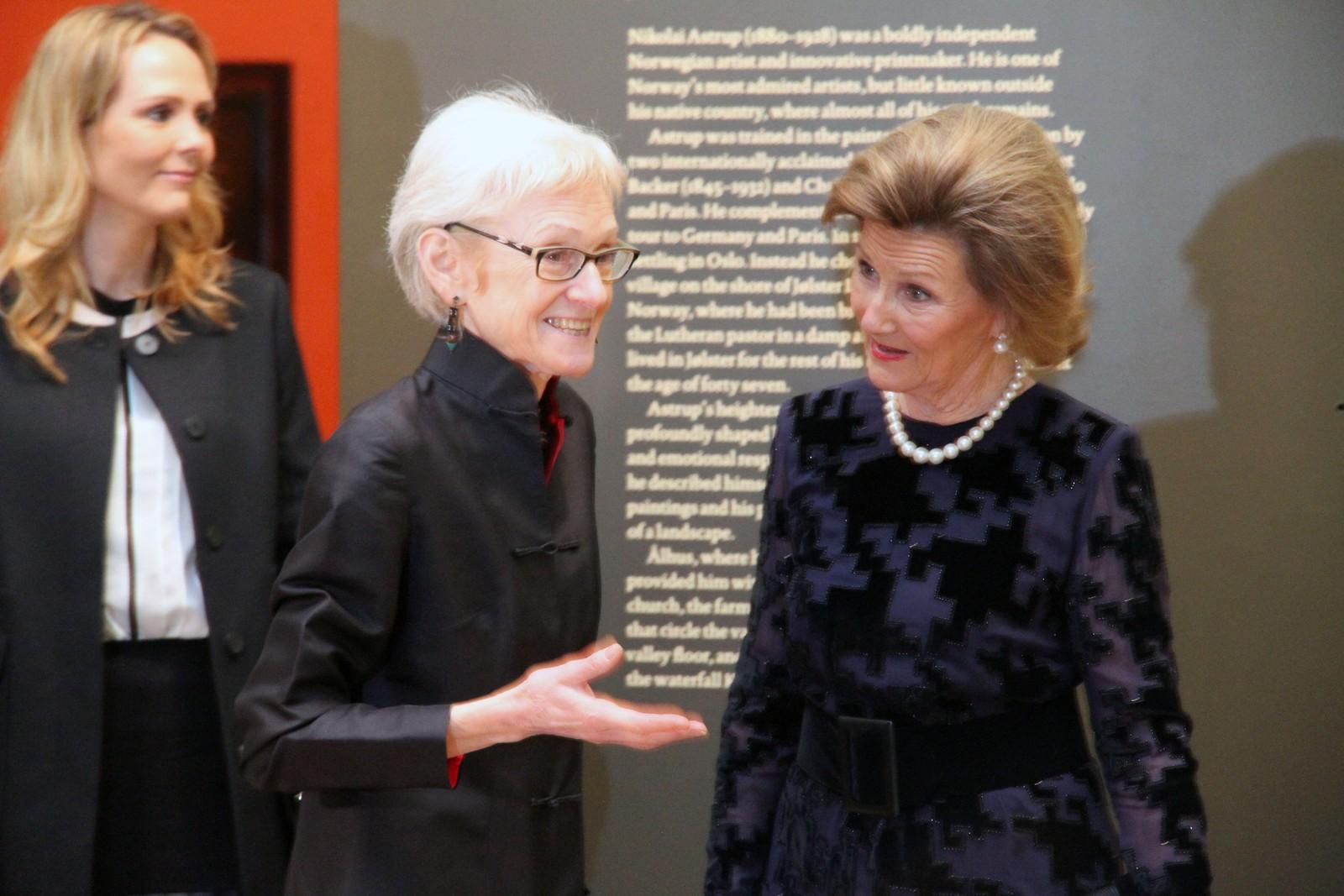 Kulturminister Linda Hofstad Helleland (t.v.) følgjer med når kurator Maryanne Stevens orienterer H.M. Dronning Sonja om arbeidet med utstillinga.