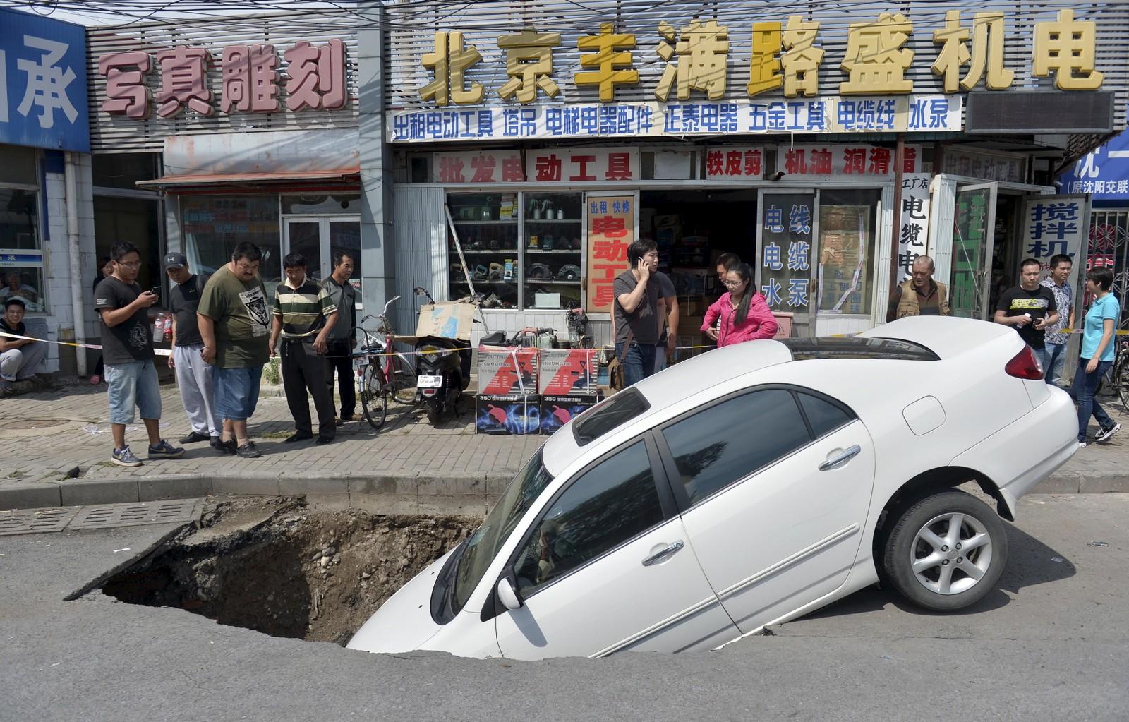 Ingen skal ha blitt skadd da et synkehull i Beijing svelget denne bilen.