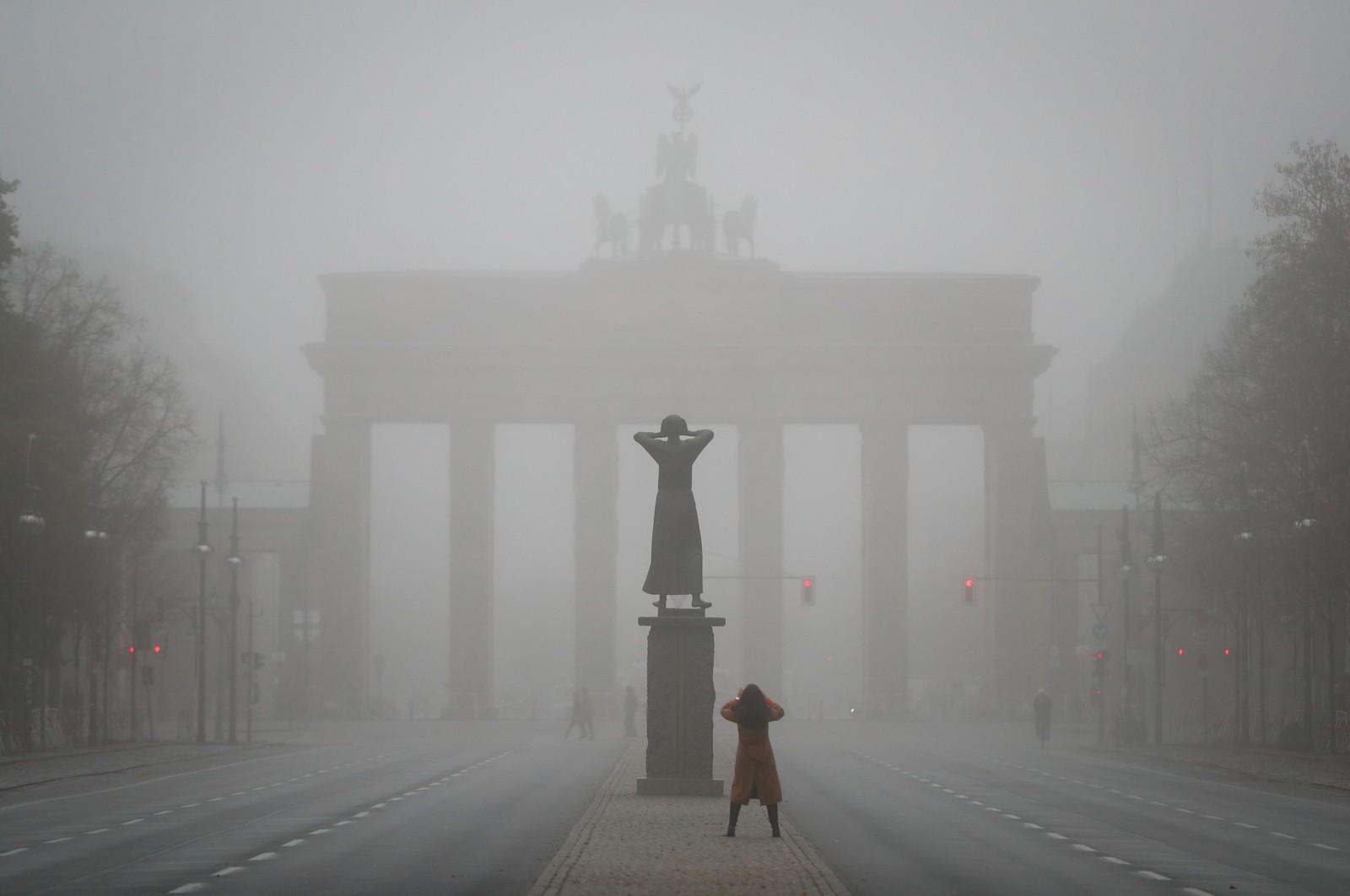 En kvinne fotograferer Brandenburger Tor i Berlin i Tyskland.