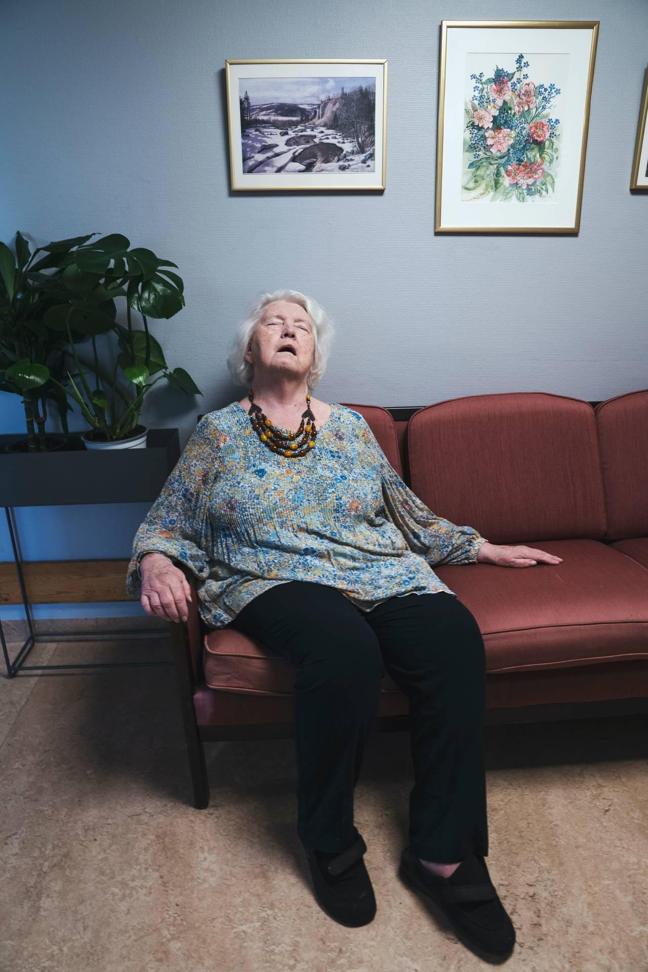 Anne Marie sitter i en eldre sofa i gangen og lukker øynene med åpen munn.