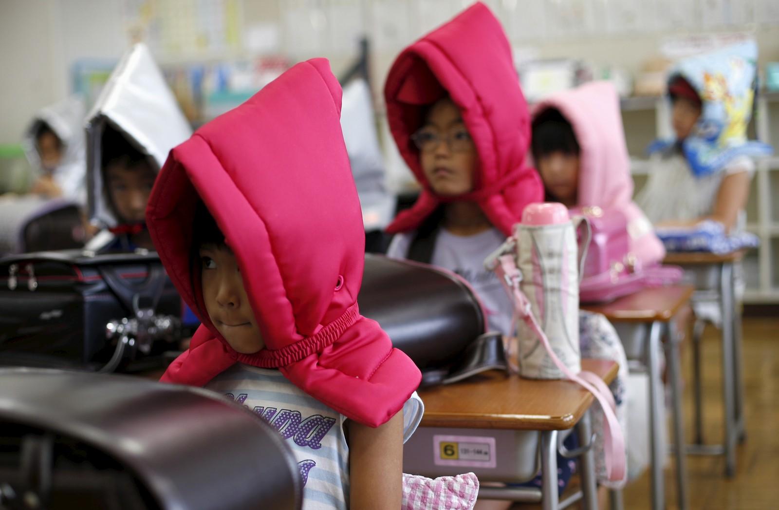 Japanske skolebarn kledd for jordskjelv-øvelse sitter klare ved pultene sine. Hettene er tenkt å beskytte hodene deres. Slike øvelser skjer 1. september hvert år til minne om det store Kanto-jordskjelvet i 1923.