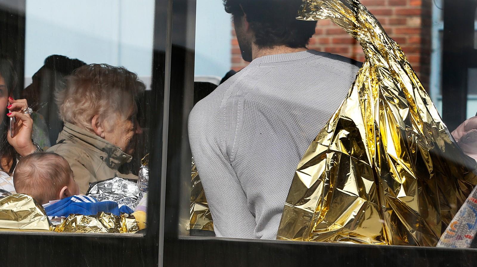 En mann og en baby sees gjennom vinduet etter terroraksjonen på flyplassen i Brussel.