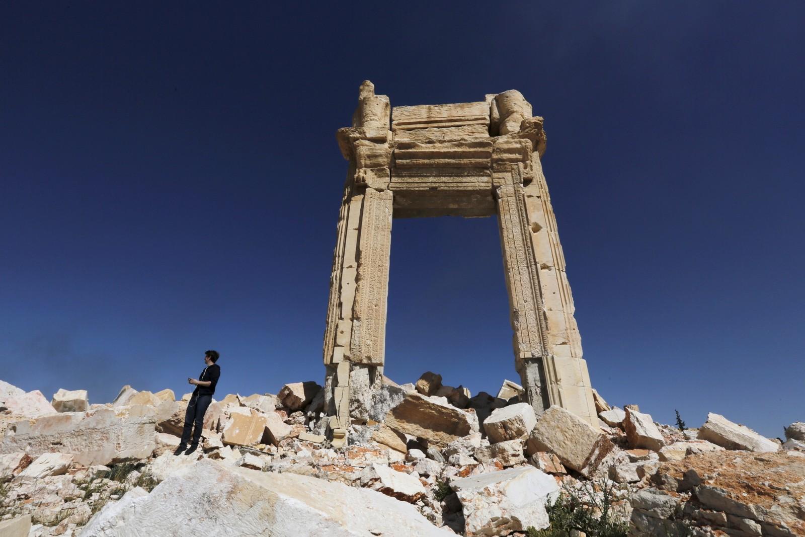 En journalist står på restene av det 2000 år gamle Bel-tempelet i Palmyra, som IS jevnet med jorden i august 2015.