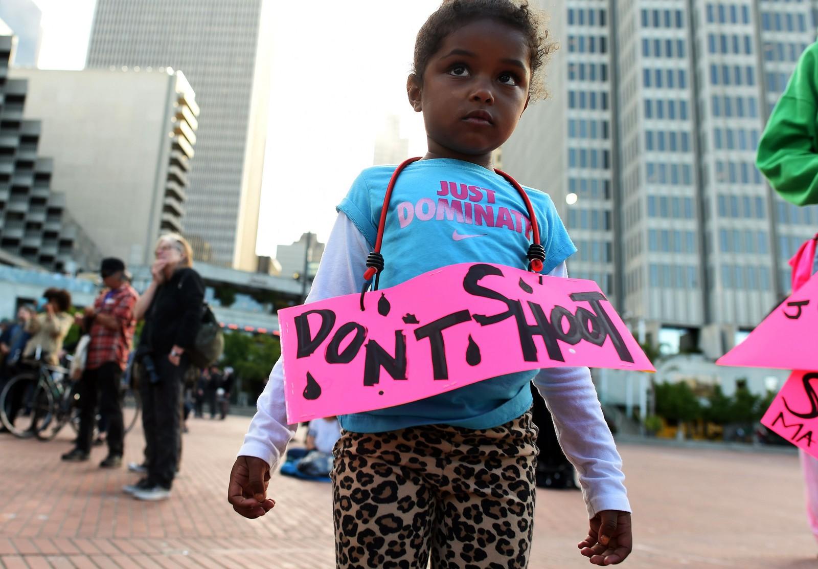 SAN FRANSISCO: Nimani Darch-Walker (3) bærer et skilt hvor det står «Ikke skyt» ved Justin Herman Plaza i sentrum av San Fransisco. I San Fransisco marsjerte 2000 demonstranter gjennom byen under et banner med teksten «Stopp rasistisk polititerror».