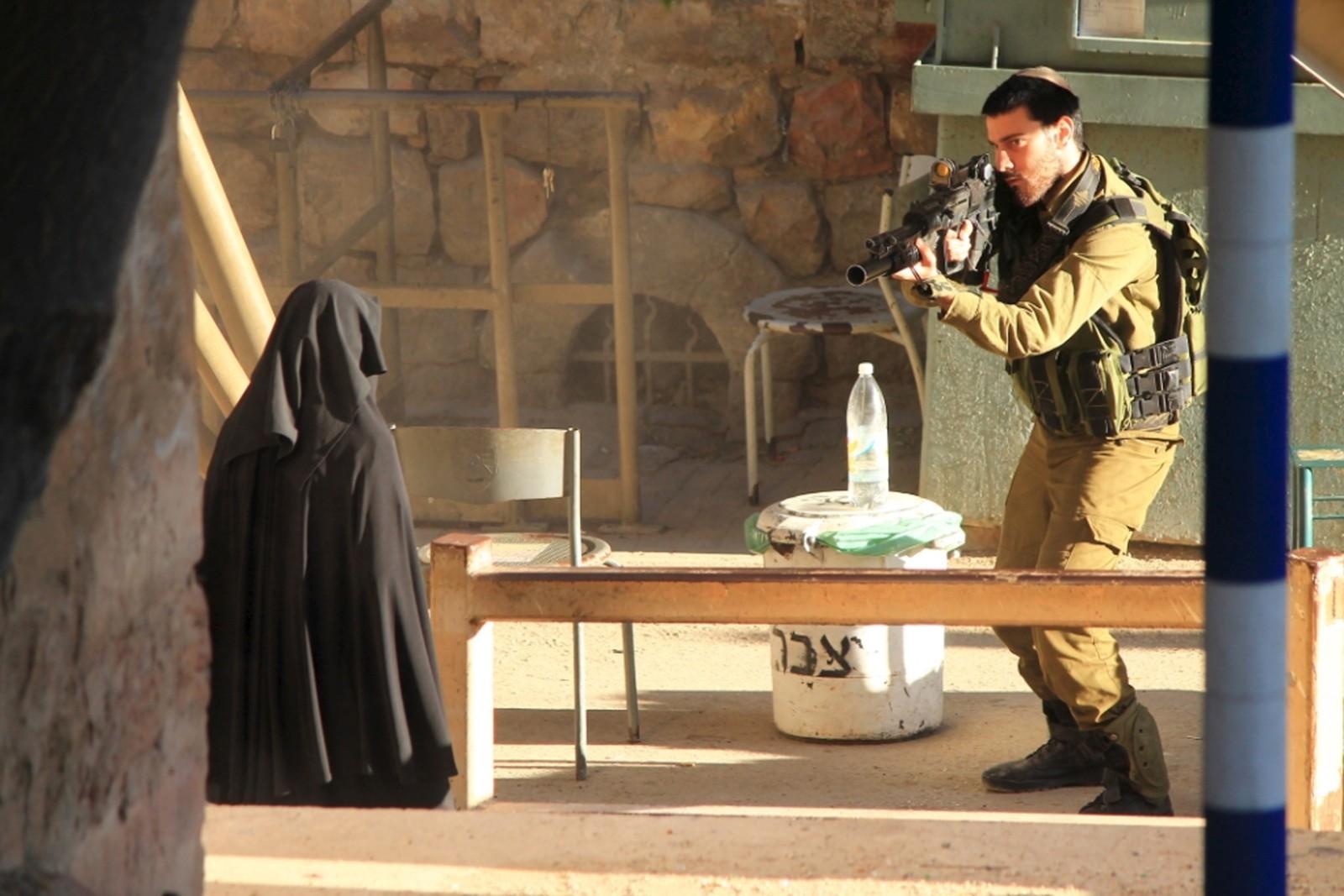 En israelsk soldat sikter på en kvinne, som hevdes å være den 19 år gamle palestinske studenten Hadeel al-Hashlamun, før hun ble skutt og drept av israelske styrker i Hebron. Israelerne sier de skjøt henne fordi hun prøvde å knivstikke en soldat. Slektningene hennes og den israelske menneskerettighetsorganisasjonen B'Tselem stiller spørsmålstegn ved denne forklaringen.
