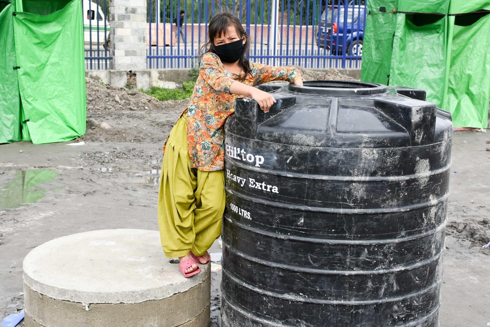 En jente lener seg på en av vanntankene i teltleiren.