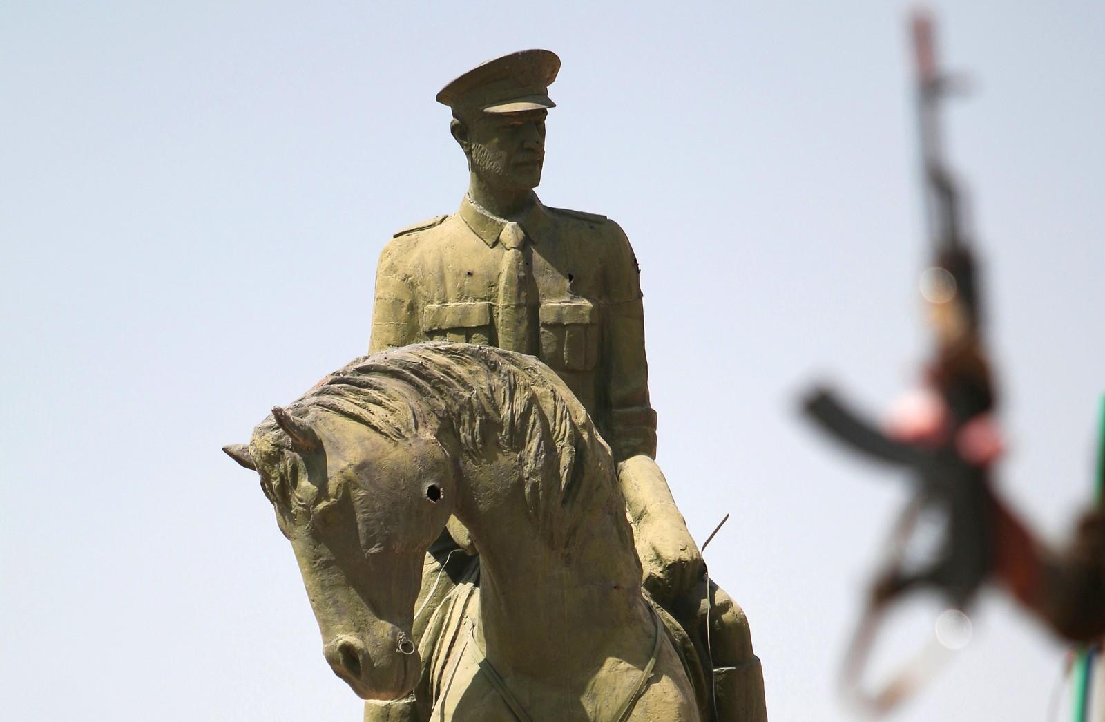 En kurdisk soldat bærer våpenet sitt ved en statue av Bassel al-Assad, broren til den syriske presidenten Bashar al-Assad. Bildet er tatt i Al-Hasakh i Syria den 23. august. Bassel al-Assad døde i en trafikkulykke i 1994.