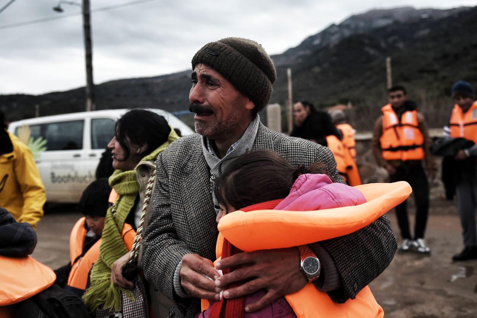 En gråtende mann holder rundt en liten pike etter å ha tatt seg i land på Lesvos 3. desember 2015.