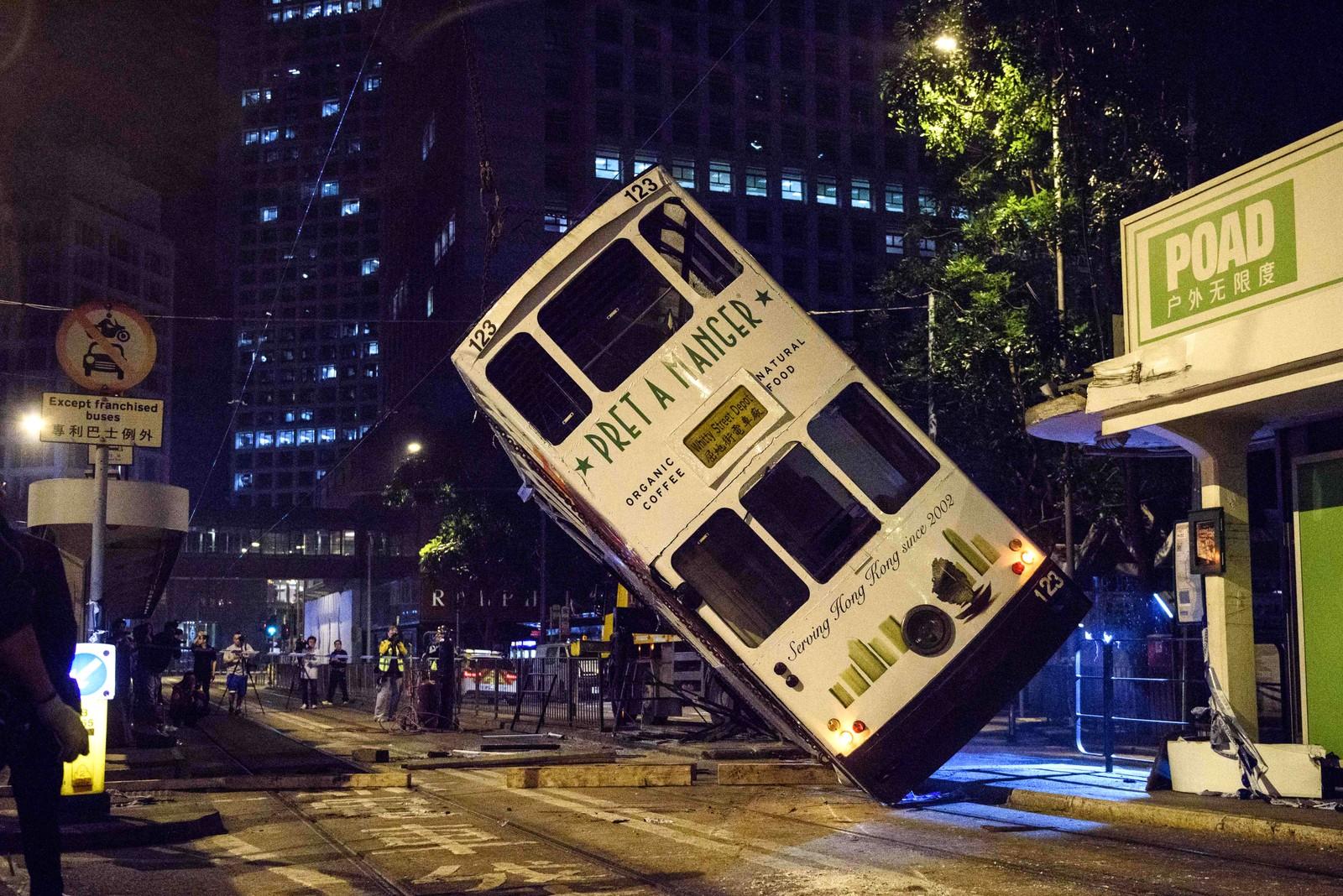 En trikk blir løftet på plass av en kran etter å ha veltet i Hong Kong.
