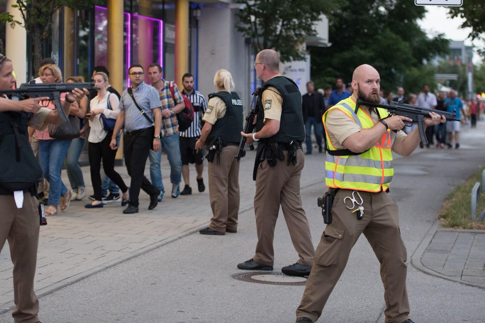 POLITIESKORTE: Bevæpnet politi eskorterer personer som forlater Olympia-kjøpesenteret etter skytingen fredag kveld. Minst åtte personer mistet livet i det politiet mistenker er et terrorangrep.