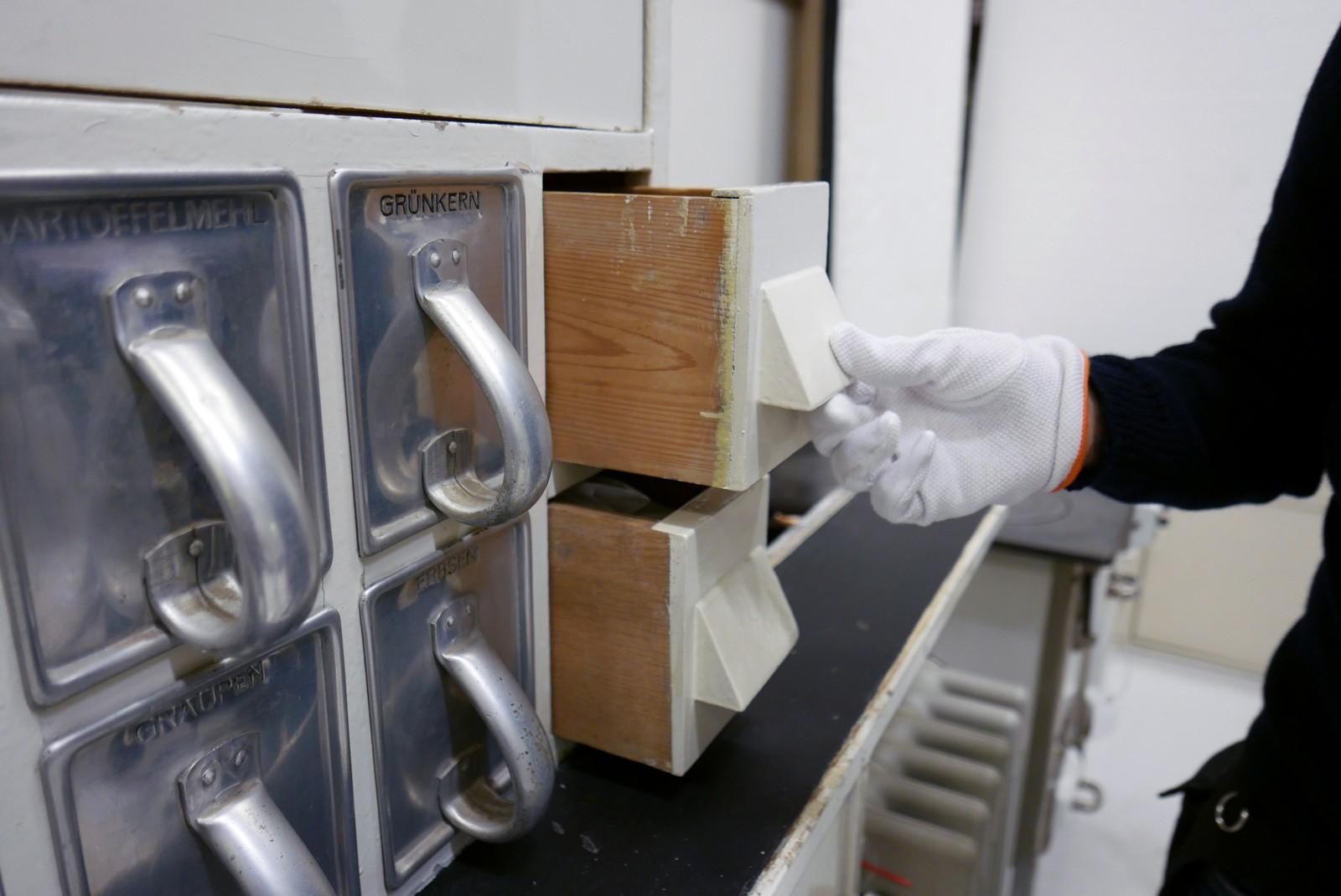 Den øverste skuffen er laget av furu og skal brukes til å oppbevare salt. Furu er valgt fordi treet holder fuktigheten unna saltet. Den nederste skuffen er laget av eik og er til oppbevaring av mel. Garvesyren til eiken gjør at melet holder seg bedre.