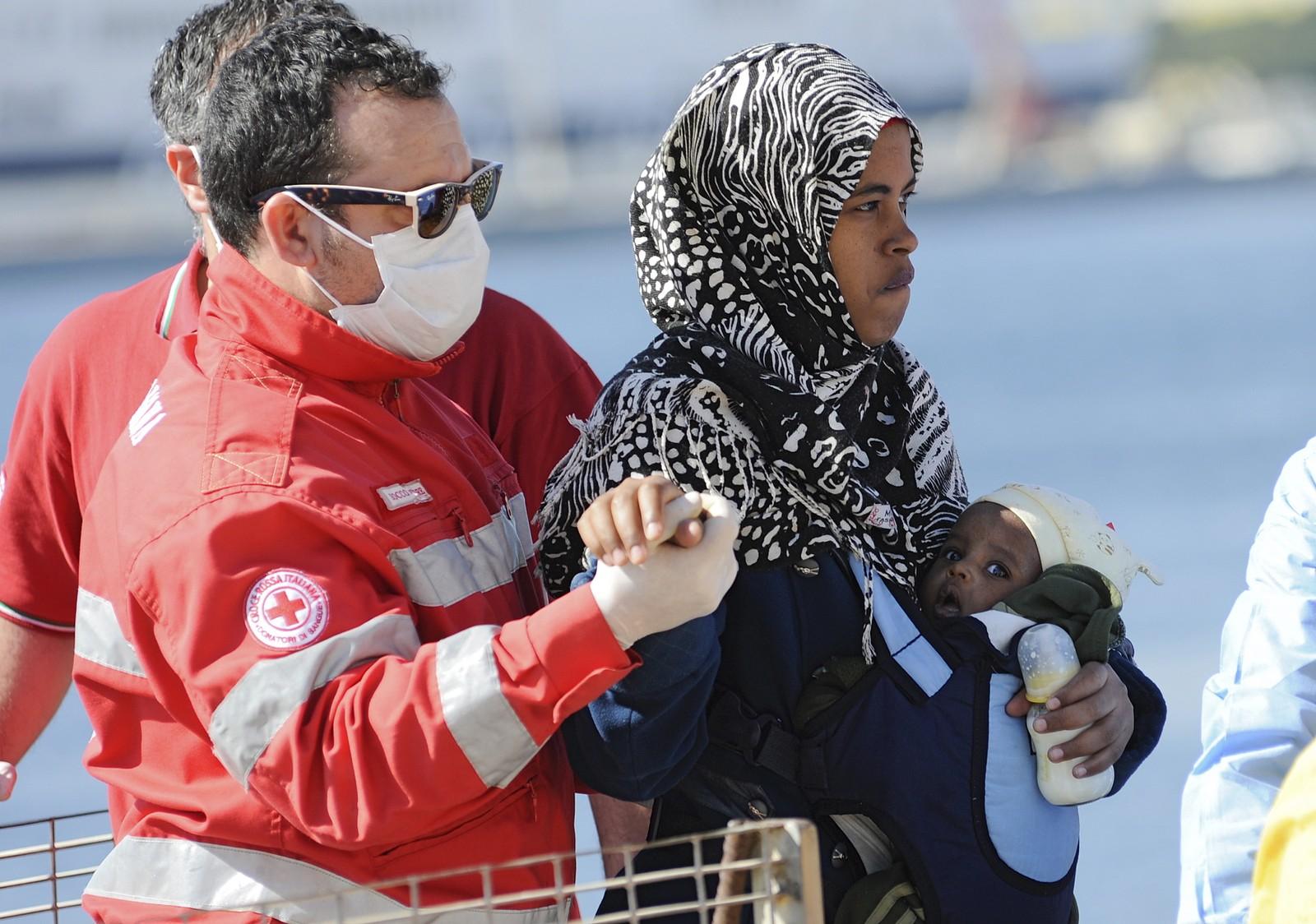 Kvinne med barn hjelpes i land i Palermo, Italia 18. april 2015.