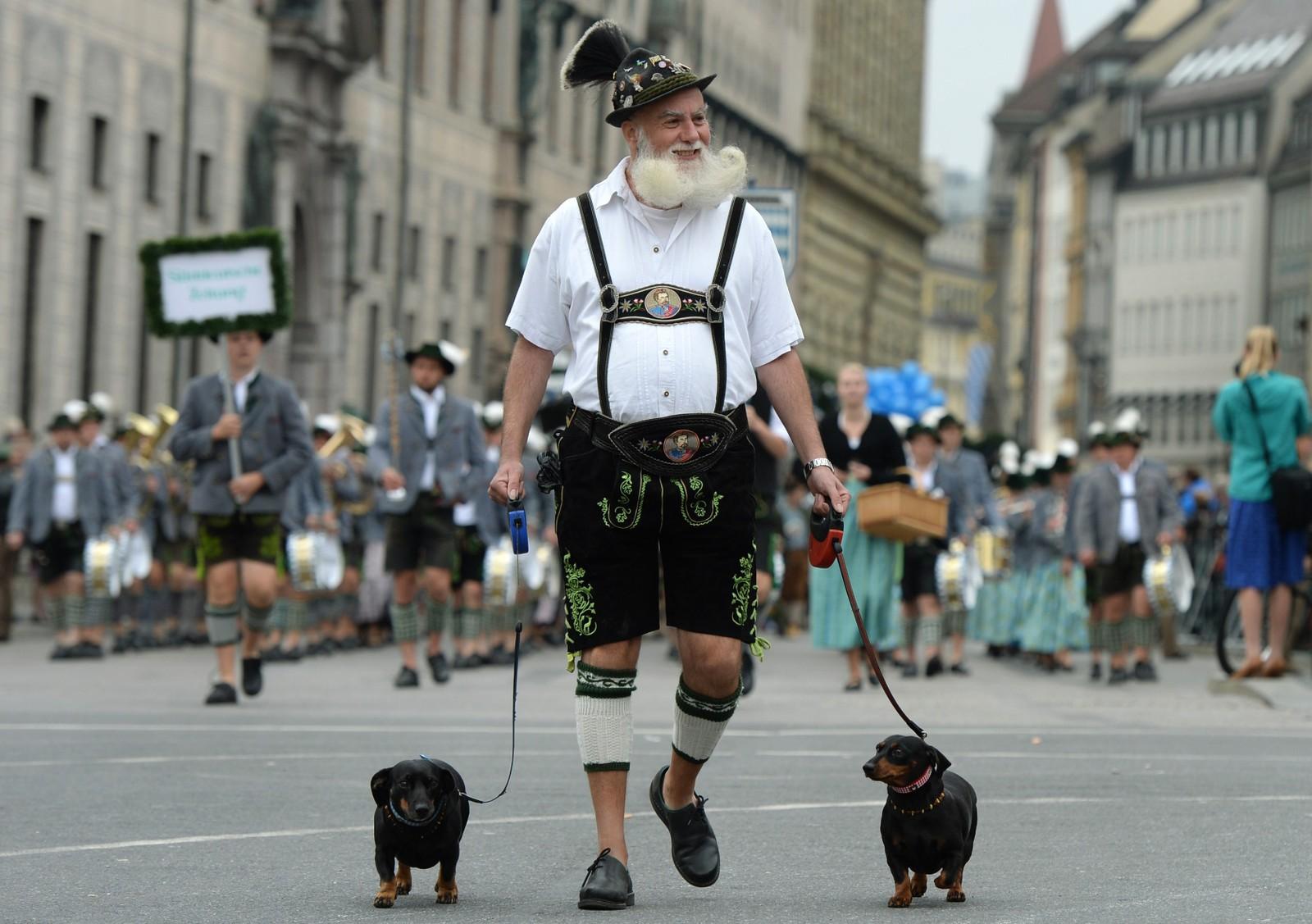 En mann i tradisjonelle lederhosen-klær er ute og går med to hunder i forbindelse med en oktoberfest-parade i Munchen. Verdens største øl-festival startet 19. september og varer til 4. oktober.