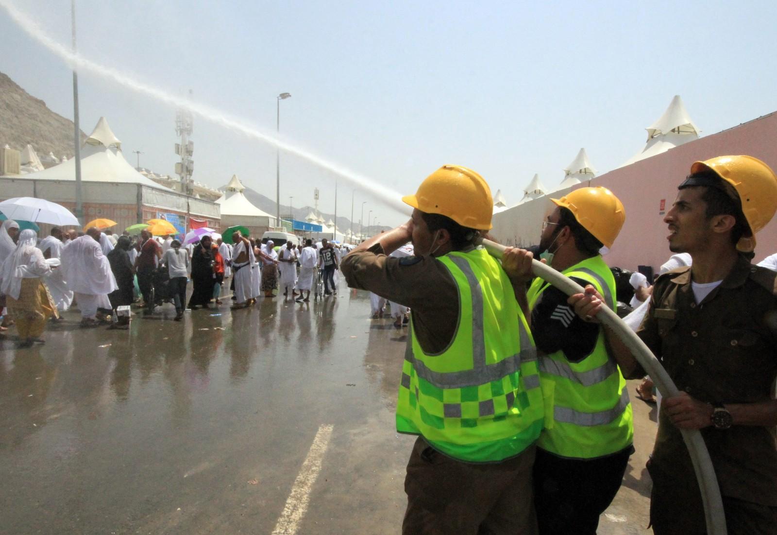 Saudi-arabisk redningspersonell spruter vann på pilegrimer for å kjøle dem ned. Det er over 40 grader i Mina i torsdag.