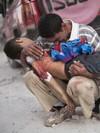 Mann med blodig barn i armene