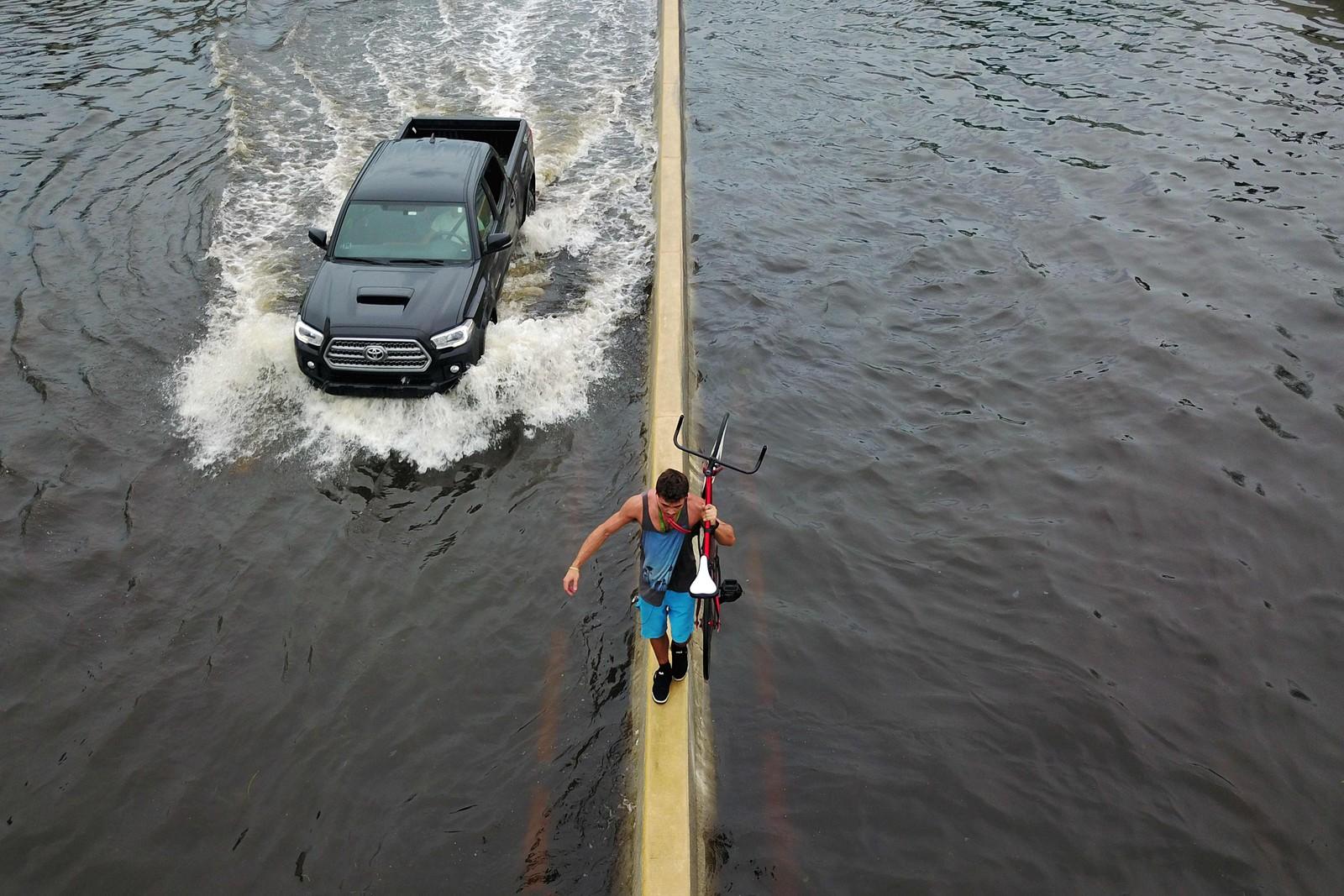 En mann balanserer på en veideler med en sykkel mens en annen velger bilen. Puerto Rico er ramma av store oversvømmelser etter at orkanen Maria traff øya denne uka.
