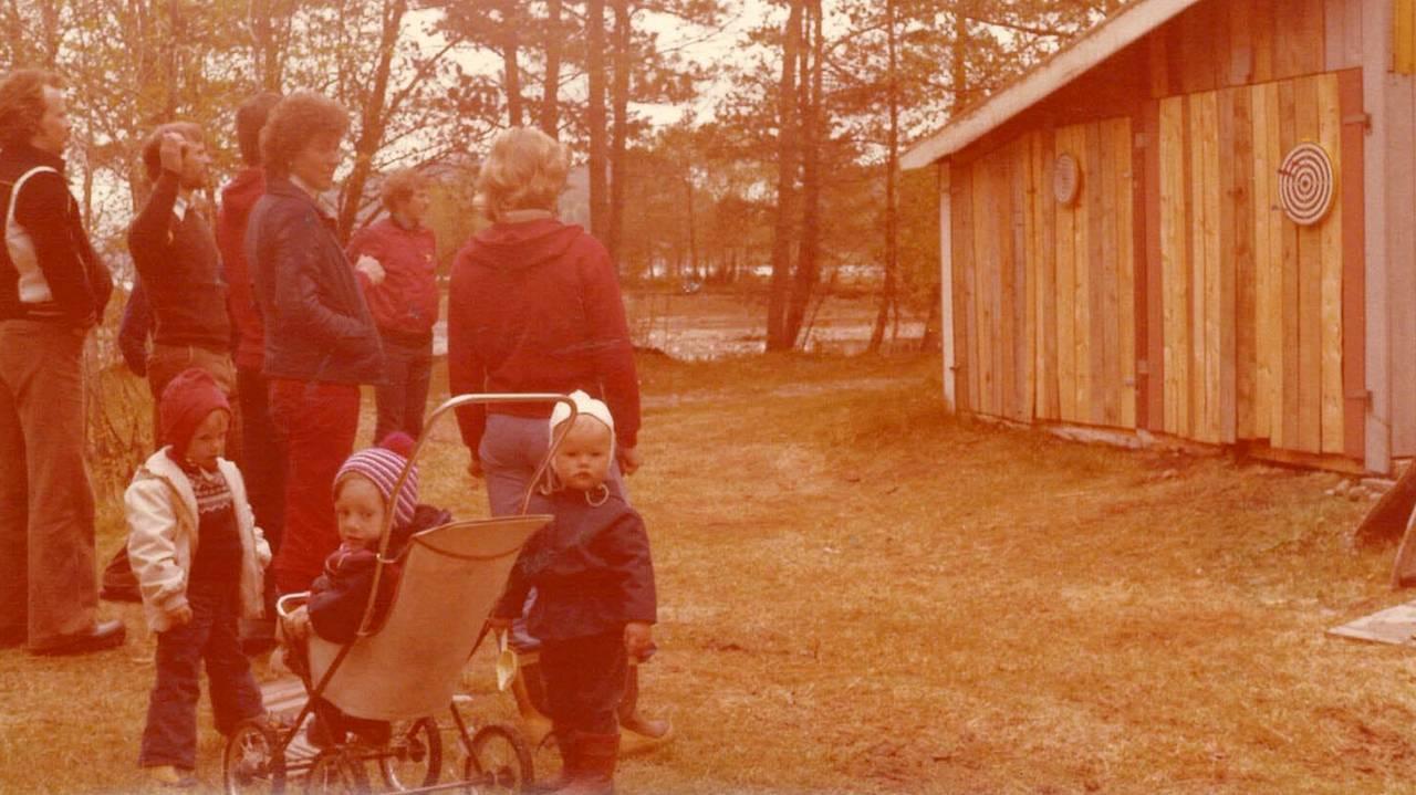 Eva Helen Angvik-Kristiansen sitter i vogn, mens andre barn på hennes alder står rundt henne