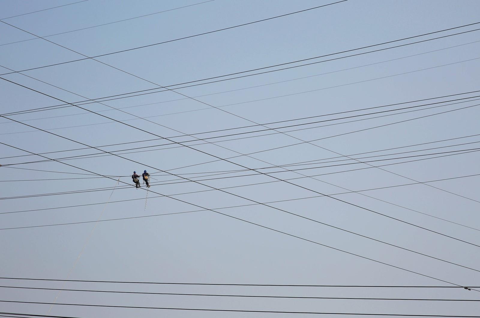 To mennesker arbeider med høyspentledninger i Tongling i Kina.