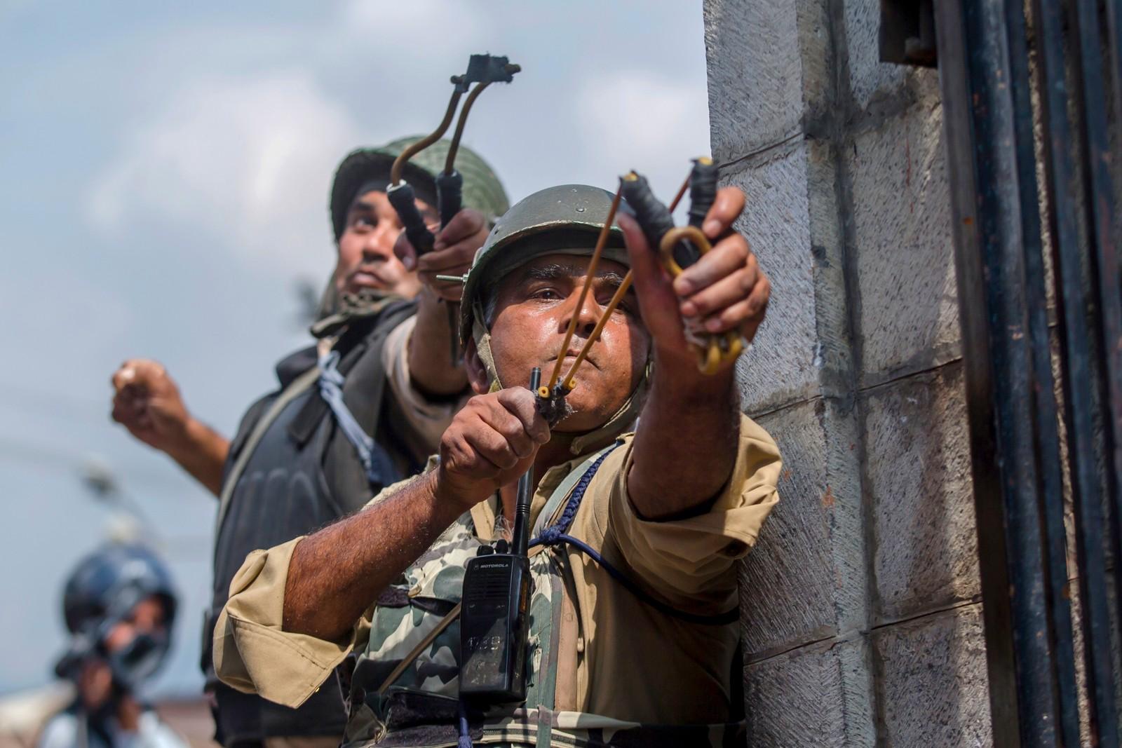 Indiske soldater skyter klinkekuler mot kasjmirske demonstranter i Srinagar. De demonstrerer mot det indiske styret i regionen.