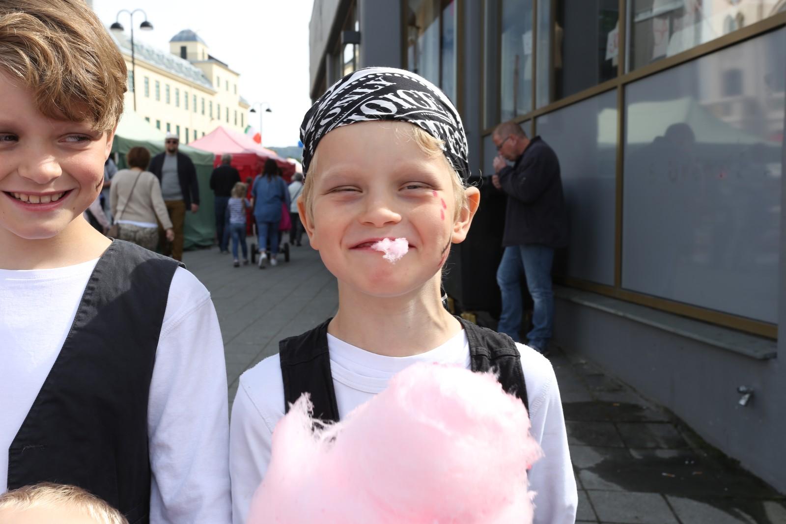 Kian Kjølsø (til høgre) likar godt sukkerspinn. Robin Kjølsø (til venstre) flirer av broren som har tatt ein stor jafs.