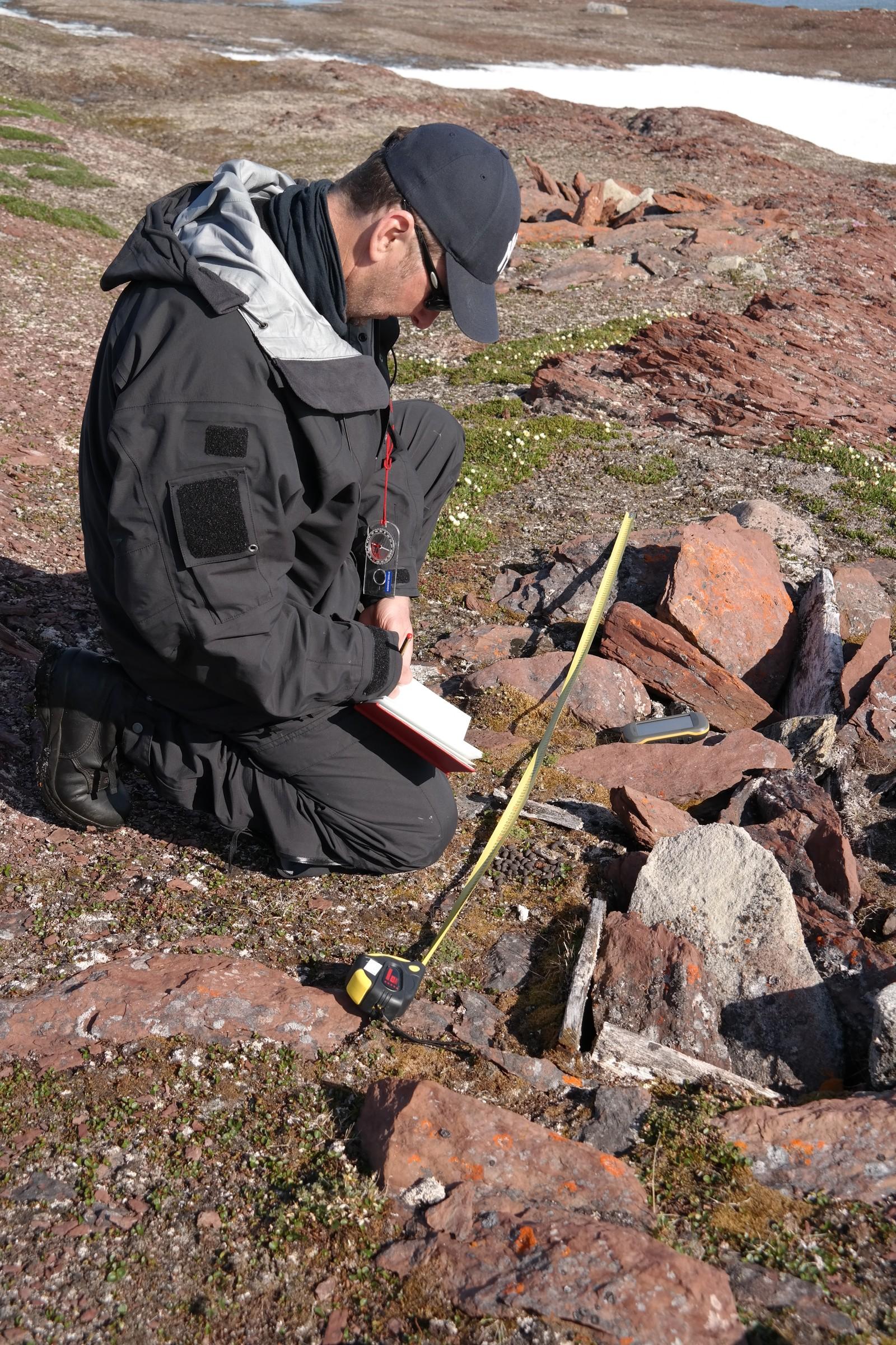 Arkeolog, Snorre Haukalid, ved Sysselmannen på Svalbard registrerer og måler opp en grav ved Reinsdyrflya.