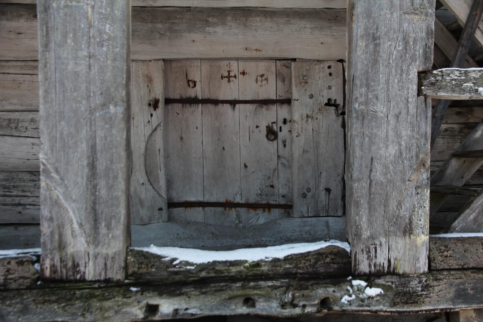 På døra er det noen tjærekryss for å beskytte maten. Spesielt på julaften var det visstnok mye skummelt ute, og da var det godt å ha slike kryss.