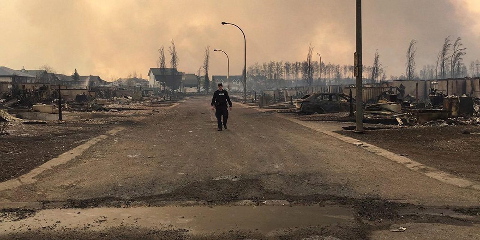 En politimann går i et område i Fort McMurray som er fullstendig nedbrent av skogbrannen i Alberta. Bildet er tatt 5. mai.