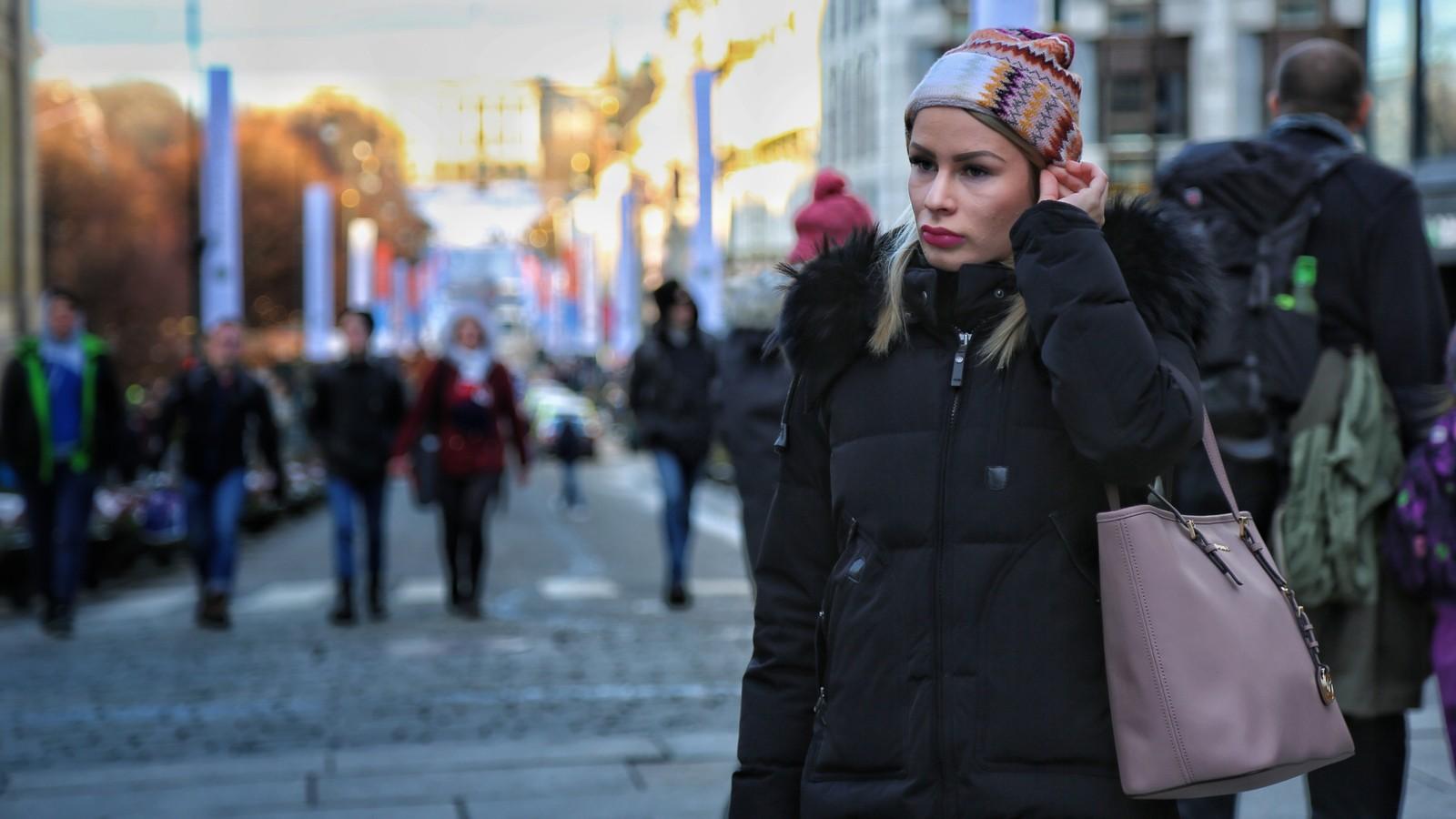 Ung kvinne på Karl Johans gate i Oslo hvor slottet skimtes i bakgrunnen. Hun har vinterklær på seg - topptue og jakke med pelskrage og ser litt ettertenksom ut.