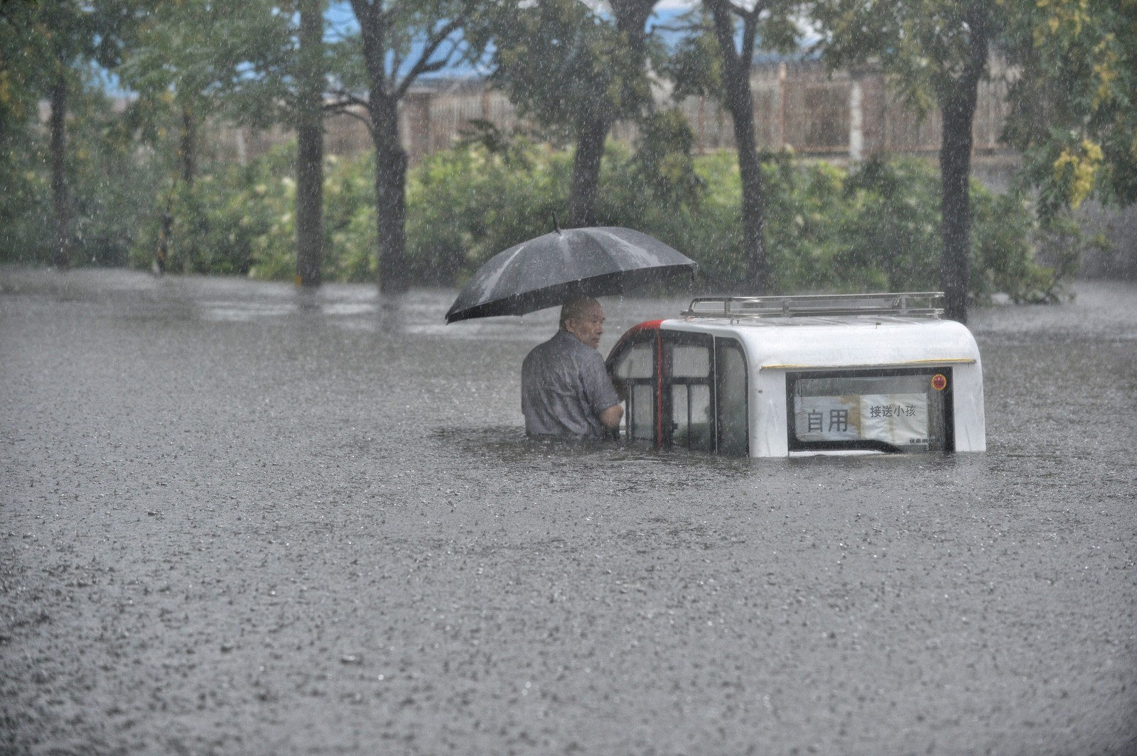 En mann og hans bil er omringet av vann i Beijing